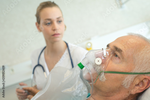 Foto close-up of senior man using oxygen mask in clinic