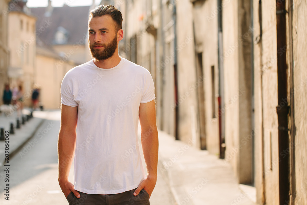 Fototapeta Hipster handsome male model with beard wearing white blank t-shirt with space for your logo or design in casual urban style