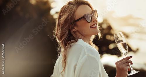 Fotografia  Smiling woman in sunglasses drinking wine
