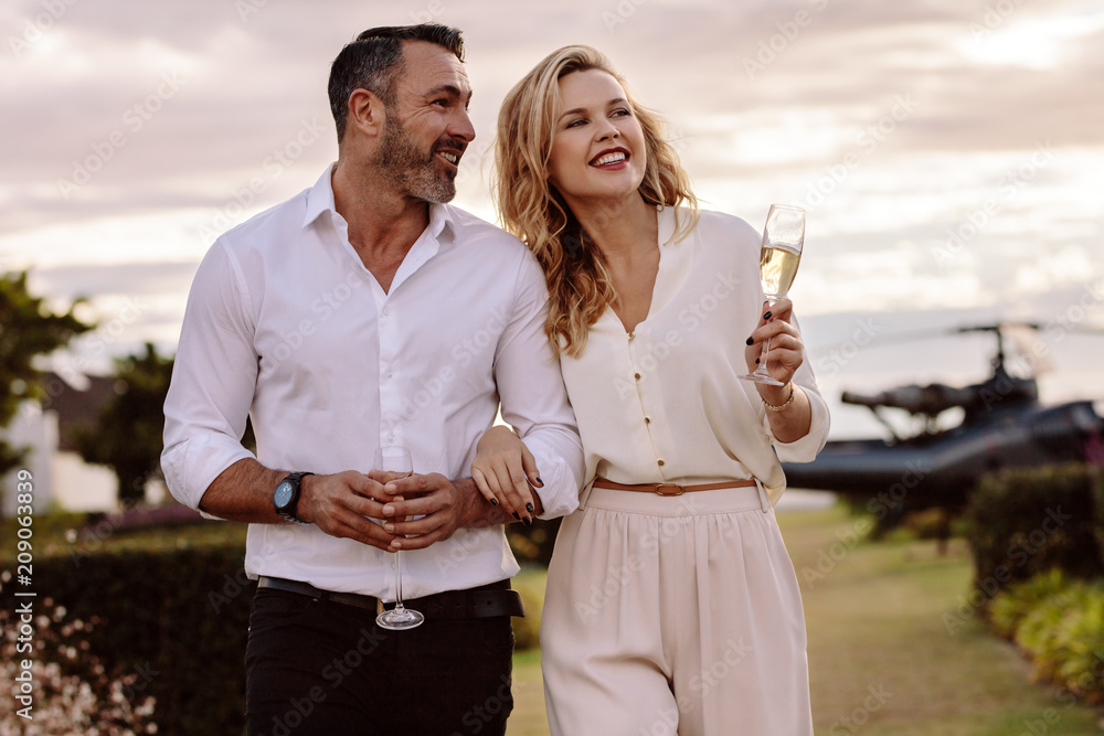 Fototapeta Elegant couple walking outdoors with wine