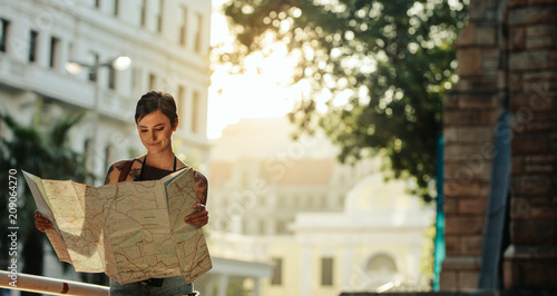 Fotografia  Woman standing outdoors holding a map