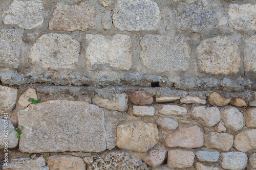 Foto op Plexiglas Stenen The wall is lined with stones. Building with cobblestones. Background of stones. The texture of the walls in the exterior. Natural stone as a building material.