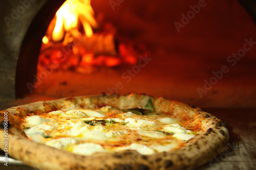 Tasty pizza near firewood oven in kitchen