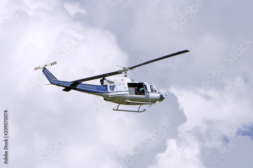 Tuinposter Helicopter Blue helicopter flight in the sky