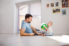 Young Father Playing With An Unhappy Baby Son At Home.