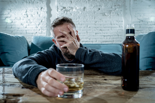 Láminas  young drunk man depressed and sad drinking whiskey at home