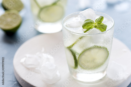 Aluminium Prints Dairy products Healthy Lemonade Lime with Fresh Mint and Ice in a Glass on Blue Background Tasty Homemade Detox Water Infused Water Close Up
