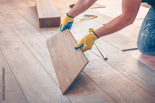Fototapeta Professional installation of floor covering, the worker quickly and qualitatively mounts a laminate board obraz