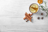 Fototapeta Dmuchawce - Cup of hot aromatic beverage with lemon and spices on table