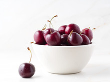 Red Dark Sweet Cherries In White Bowl On Stone White Table, Side View.
