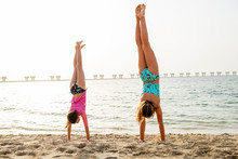 Two Young Girls Doing Handstand On The Beach In Dubai