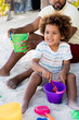Ethnic man playing with son in sand