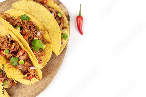 Overhead closeup photo of Mexican tacos with pulled meat, avocado, chili peppers, cilantro, with copy space, on white