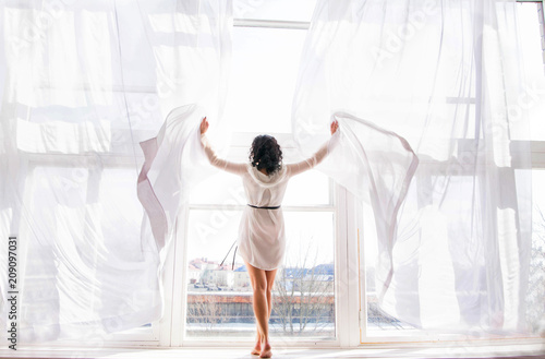 Photo  the young woman stands on the window among the open curtains