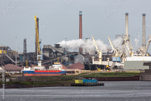 Fototapeta Big steel factory in harbor IJmuiden with cargo carrier in front, The Netherland