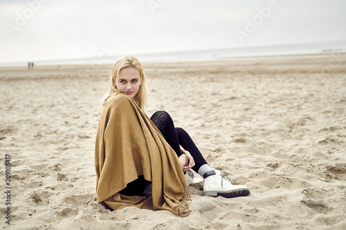 Netherlands, portrait of blond young woman sitting on the beach