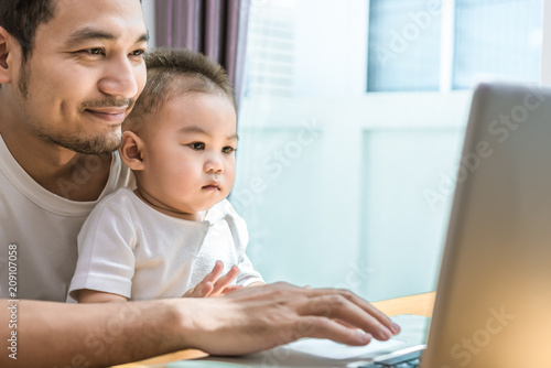 Fotografía  Single dad and son using laptop together happily