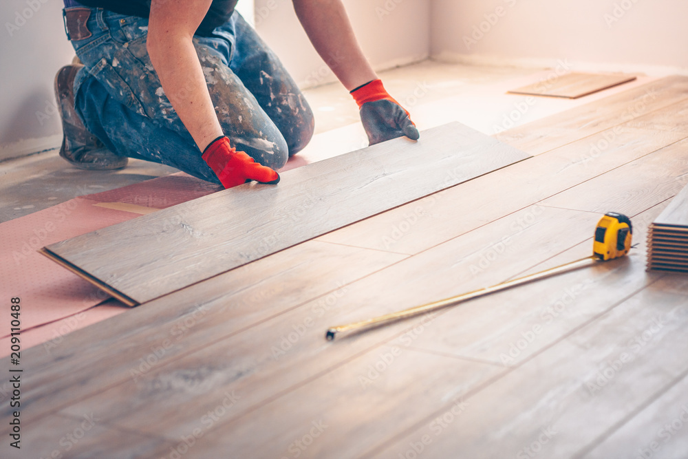 Fototapeta Worker professionally installs floor boards