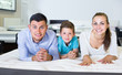 Happy family of three choosing right mattress in home furnishings store