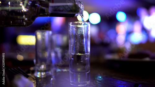 Photo Male hand pouring in huge shot of vodka, alcoholism issues, failed abstinence