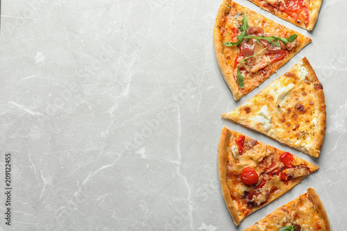 Slices of delicious pizza on light background, top view