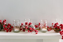 Red Berry Christmas Garland And Votive Candles On A Mantlepiece. Copy Space.