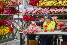 Disabled Female Florist Arranging Gerbera Daisies
