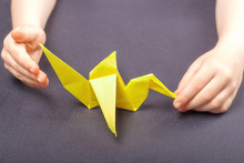 Paper Yellow Crane Origami In Children's Hands On The Background Of The Desktop. The Concept Of Children's Creativity, Development Of Assiduity And Calm Games