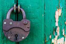 Part Of A Green Old Door Closed On A Vintage Rusty Metal Padlock