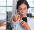 Middle aged woman using smartphone pointing with finger to the camera and to you, hand sign, positive and confident gesture from the front