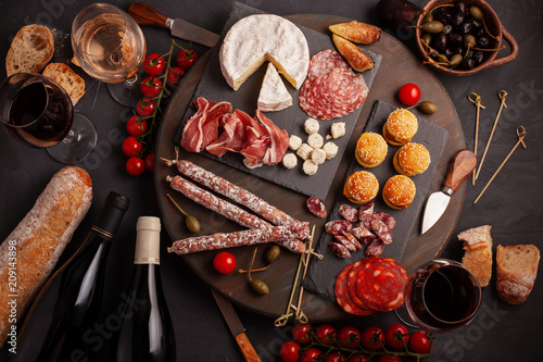 Poster de jardin Buffet, Bar Appetizers table with differents antipasti, cheese, charcuterie, snacks and wine. Mini burgers, sausage, ham, tapas, olives, cheese and baguette over grey concrete background. Top view, flat lay