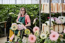 Confident Florist Sitting In Wheelchair At Greenhouse
