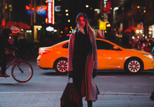Young Woman Standing On Busy City Street At Night