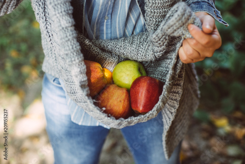 woman holds a basket with a fruit