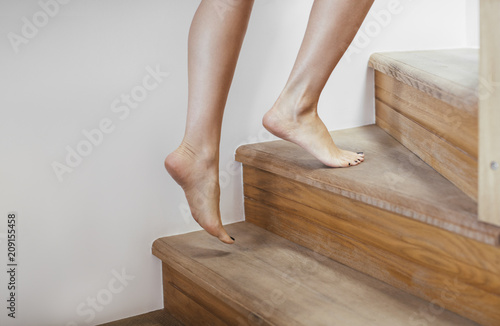 Feet of a Woman Climbing up the Stairs