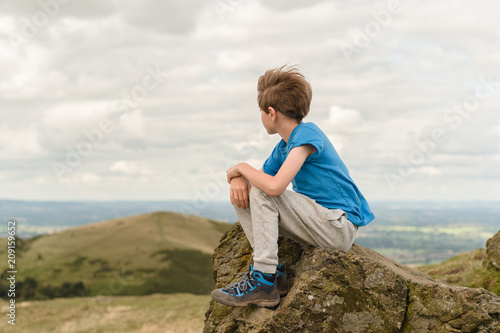 Tween boy sitting at the summit of a hill after his climb