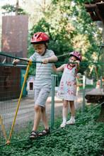 Adorable Boy And Girl Having Fun On A Ropes Course