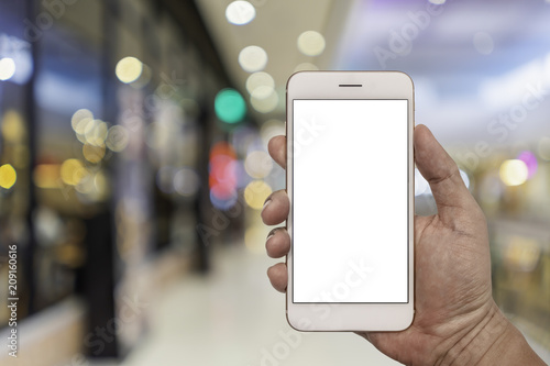 Fotografie, Obraz  Hand holding smartphone with blur interior in shopping mall.