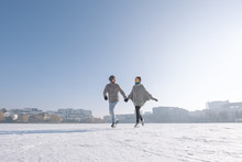 Young Couple Ice Skating On The Lake On A Bright Day