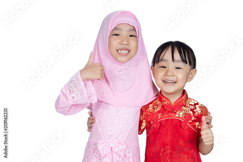 ee54b1382 Asian Chinese little sisters wearing cheongsam and traditional Malay costume  with thumbs up