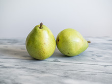 Two Green Pears On White Marble Countertop.
