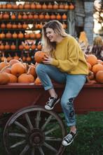 A Young Woman Holding A Pumpki...