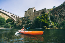 Paddler In A Canoe On A River In A Lush Green Valley Near A Medieval Village And Bridge