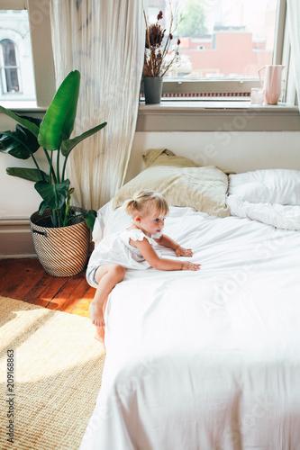 Toddler Climbing onto a Bed