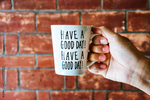 "Photo  close up of male hand holding white coffee or tea cup with text ""HAVE A GOOD DAY"
