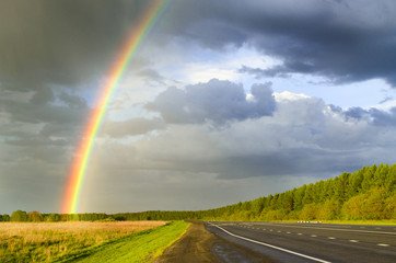wet highway after rain with a rainbow against the backdrop of a rainy sky