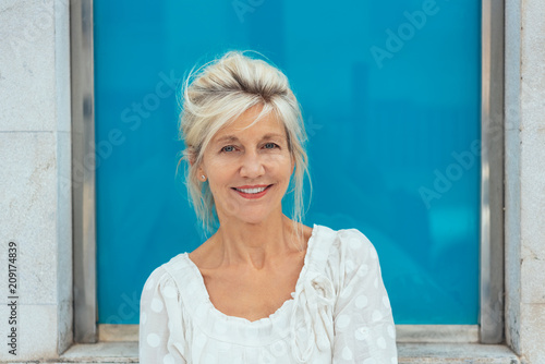 Fotografía  Smiling blond senior woman in white top