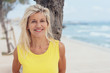 canvas print picture - Attractive tanned blond woman standing on a beach