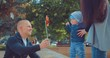 Happy little kid is playing with his parents in the park. Mom supports the baby, dad shows the baby a toy