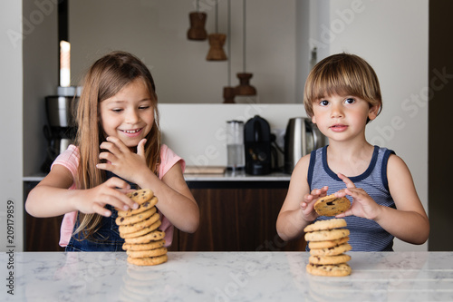 Kids piling up cookies at kitchen counter